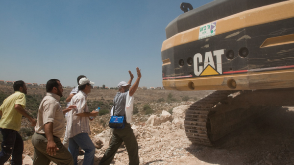 Activists in the West Bank village of Ni'lin block a Caterpillar excavator used in the construction of the apartheid wall