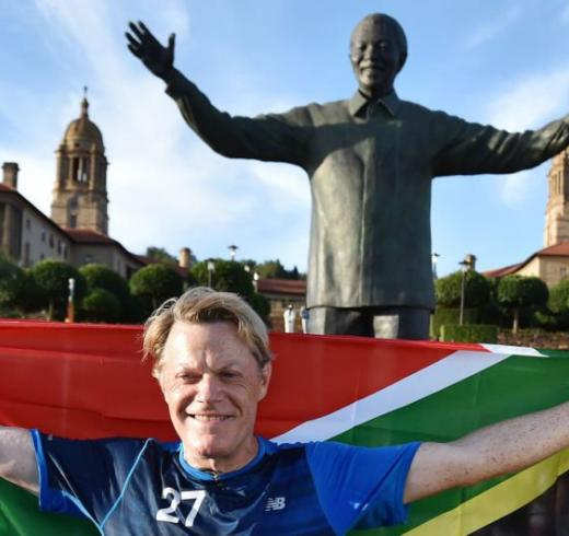 British comedian Eddie Izzard holds a South African flag beneath a statue of former president Nelson Mandela at the government's Union Buildings in Pretoria, South Africa, Sunday, March 20, 2016. (AP Photo)