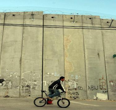 Palestinian boy on a bike near Israel's apartheid wall