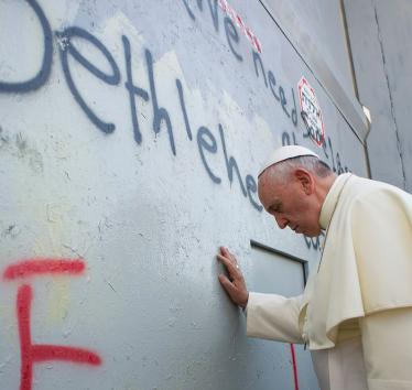 Pope Francis touches the wall on his way to celebrate a mass in Manger Square, in the Palestinian city of Bethlehem